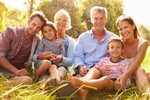 Multi-generation family relaxing together outdoors, smiling to camera